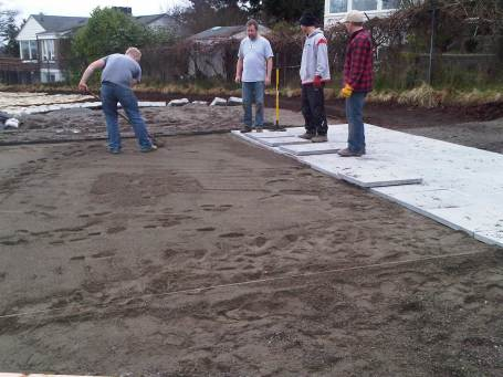 Volunteers help lay the new pavers from Mutual Materials